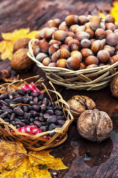 Nuts in baskets on wooden background - бесплатный image #301997