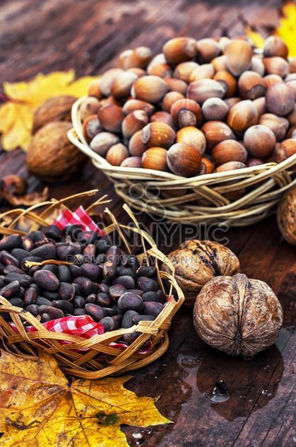 Nuts in baskets on wooden background - Free image #301997