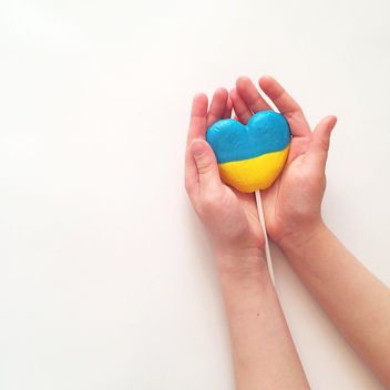Hands holding lollipop in colors of Ukrainian flag on white background - бесплатный image #329297