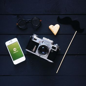 Smartphone with Clashot logo, retro camera and accessories on dark wooden background - image #329307 gratis