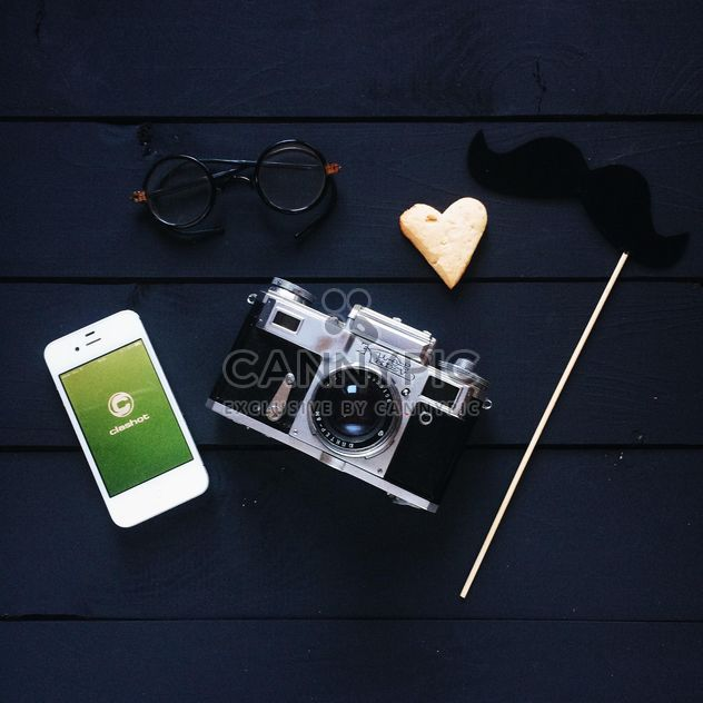 Smartphone with Clashot logo, retro camera and accessories on dark wooden background - Free image #329307