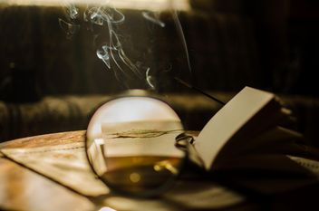 Autumn yellow leaves through a magnifying glass with incense sticks and book - бесплатный image #330407