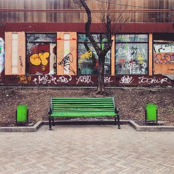 Green bench in street - image #332077 gratis
