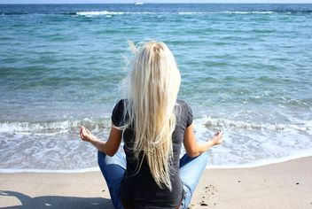 Woman meditating on sea shore - бесплатный image #333137