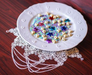 Decorative stars, tinsel and cubes on the plate - image #342077 gratis