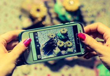 Smartphone decorated with tinsel in woman hands - image gratuit #342177