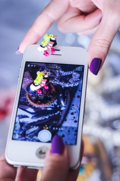 Smartphone decorated with tinsel in woman hands - бесплатный image #342187