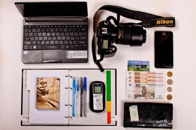 Still life of Laptop, camera, smartphone, office items and money over white background - бесплатный image #342477
