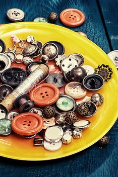 Colored buttons and sewing thread on the plate - image #342597 gratis