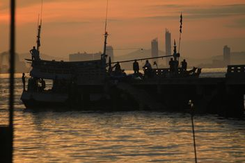 People and boat on sea at sunset - image #344517 gratis