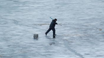 Fisherman during winter fishing on frozen river - Free image #344627