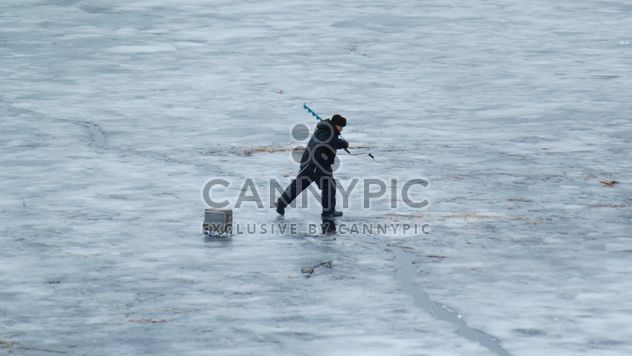 Fisherman during winter fishing on frozen river - бесплатный image #344627
