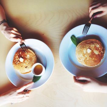 Hands of couple eating pancakes for breakfast - бесплатный image #345027