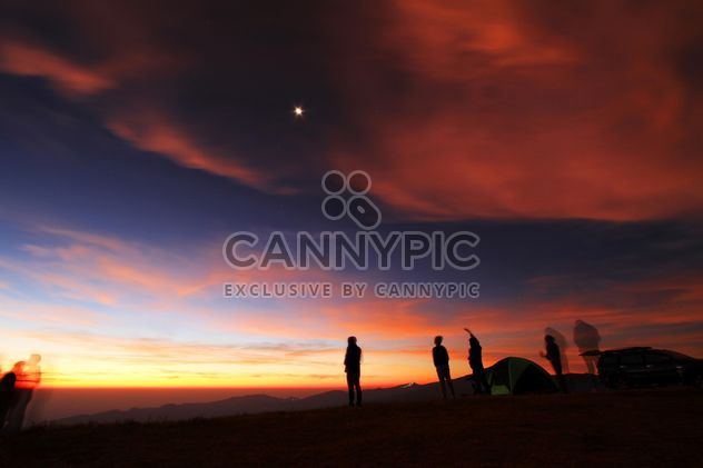 Silhouettes of people in mountains at sunset - Free image #345117