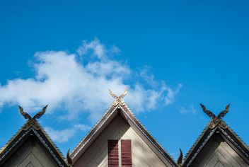 Roof of Thai temple against blue sky - бесплатный image #347307