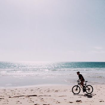 Man riding bicycle along coast - Free image #394807