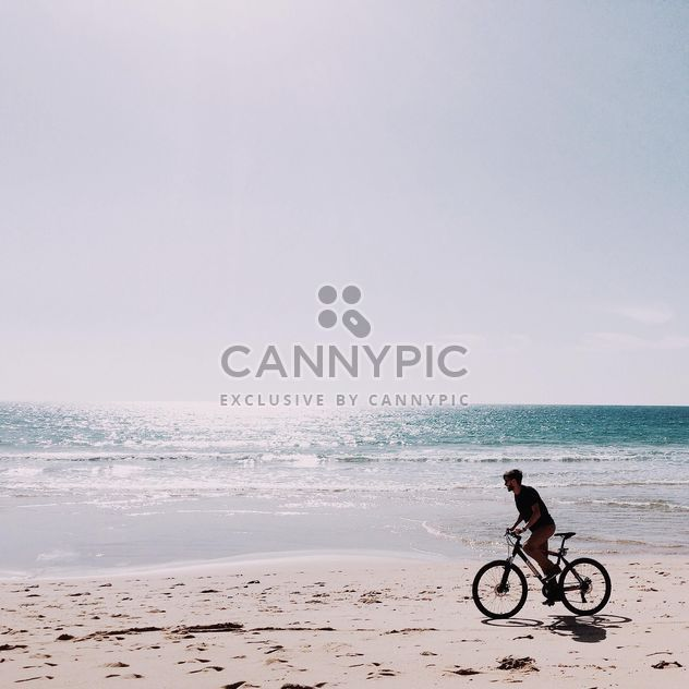 Man riding bicycle along coast - image #394807 gratis