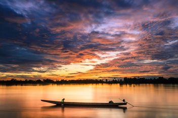 Man in boat at sunset - image #451937 gratis