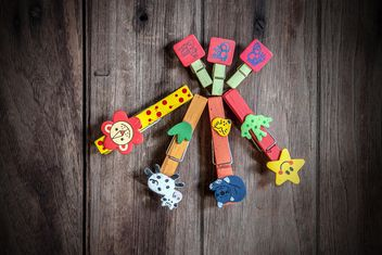 Colored clothespins on wooden background - image gratuit #452417