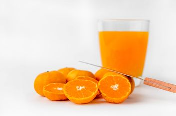 orange juice in glass and knife on white background - image #452527 gratis
