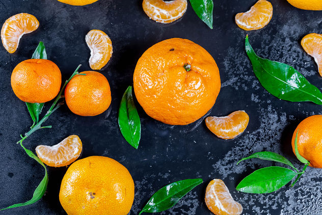 Fresh mandarin oranges fruit with leaves on dark table - бесплатный image #457477