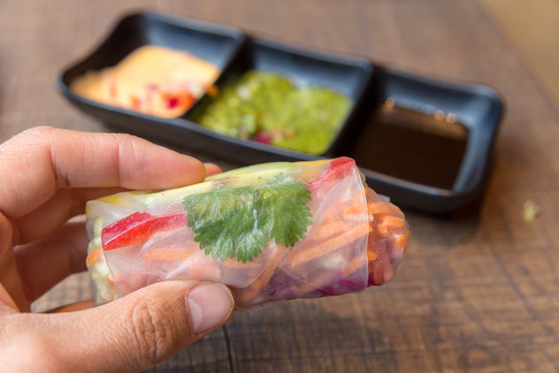 Hand holds a summer roll filled with avocado, mango, paprika, red cabbage, carrots and rice noodles with various sauces in the background - Kostenloses image #460977